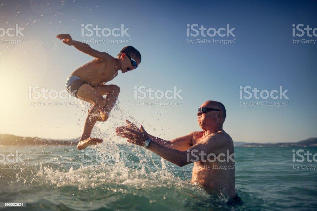 Senior homme jouant avec petit-fils en mer - Photo