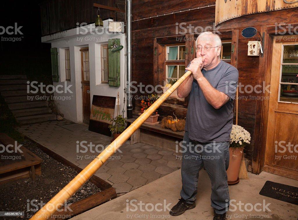 senior man plays Swiss Alpen horn on vacation stock photo