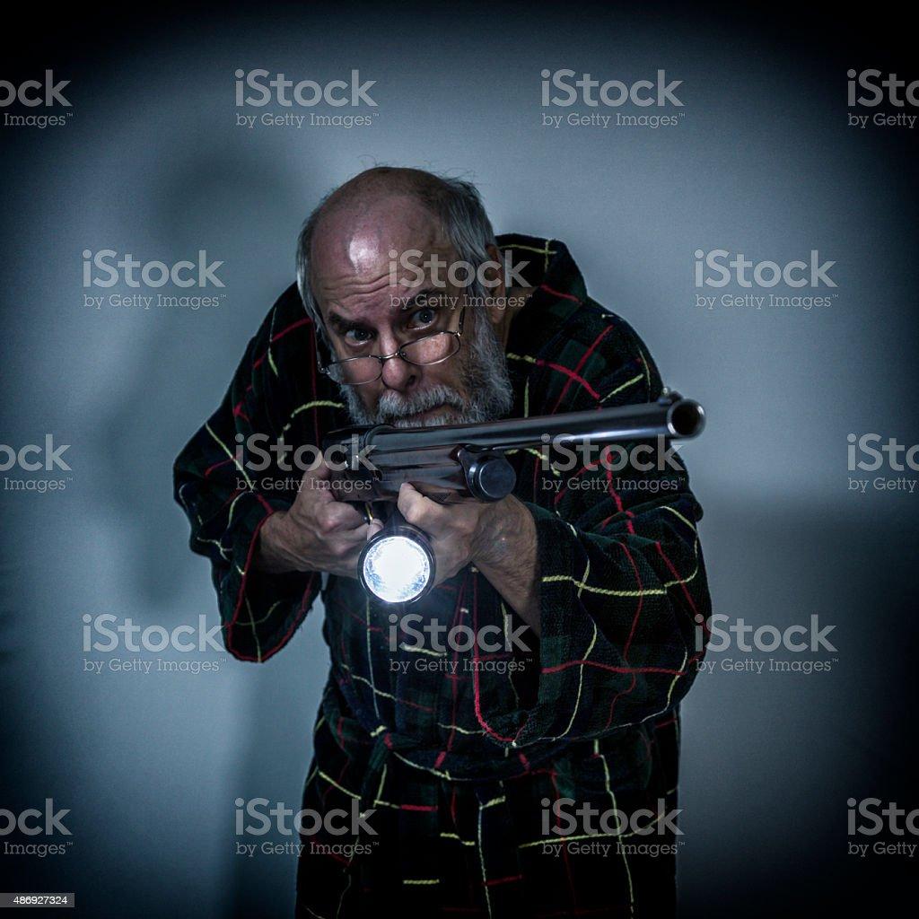 Senior Man Pointing Shotgun and Flashlight in Dark Room stock photo