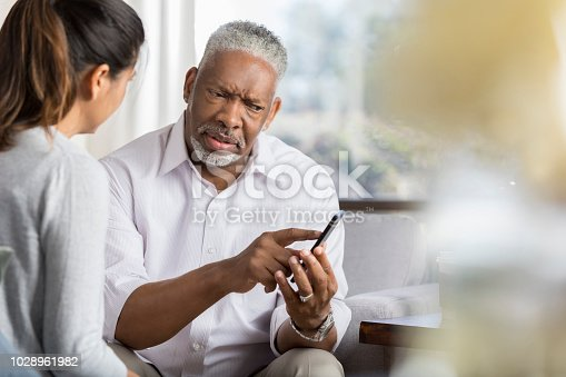 istock Senior man points at something on smartphone 1028961982