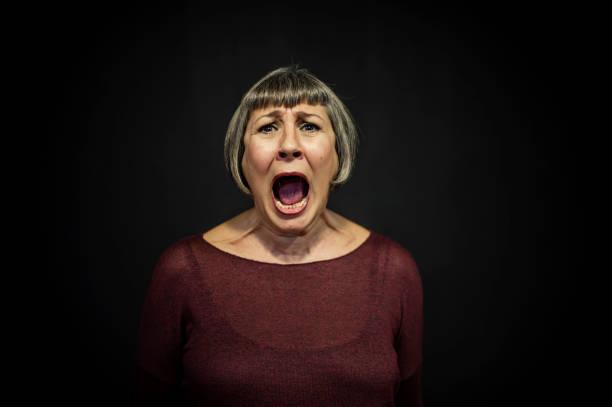 senior man portrait on black background - mujer gritando fotografías e imágenes de stock