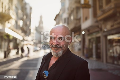 Senior man posing in city lifestyle image looking at camera with suit clothes