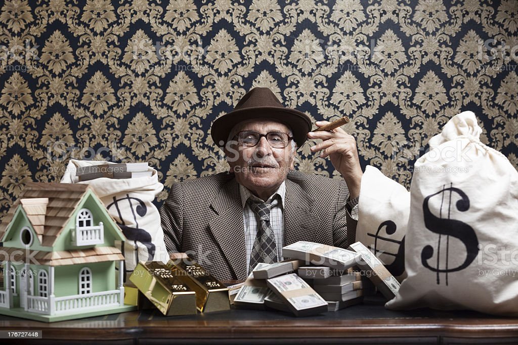 Senior man posing with gold ingots and money bags royalty-free stock photo
