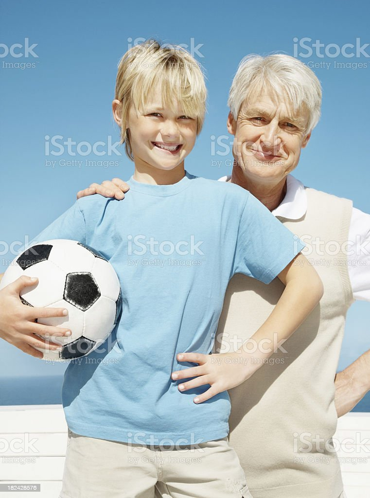 Senior man posing with his grandson holding a football royalty-free stock photo