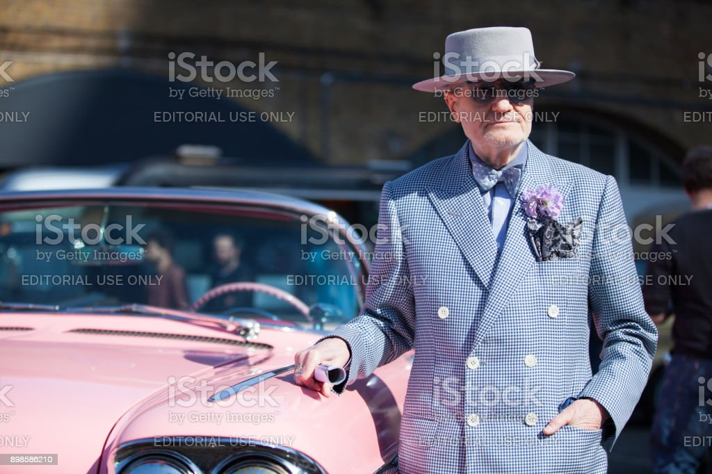 Senior man posing with his Pink 1960 Cadillac