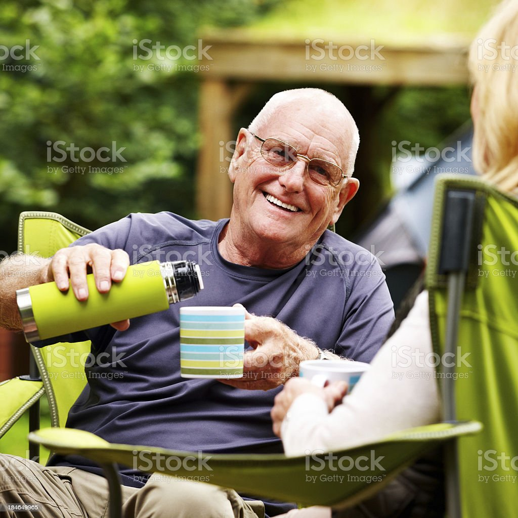 Senior Man Pouring Coffee While Camping royalty-free stock photo