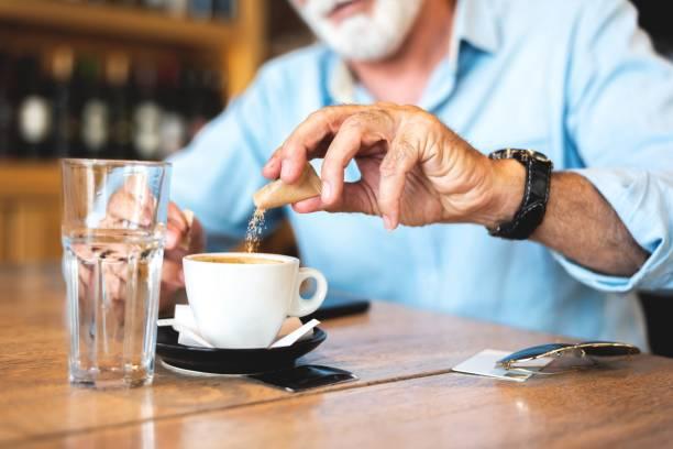 Senior man pouring sugar into coffee at restaurant stock photo