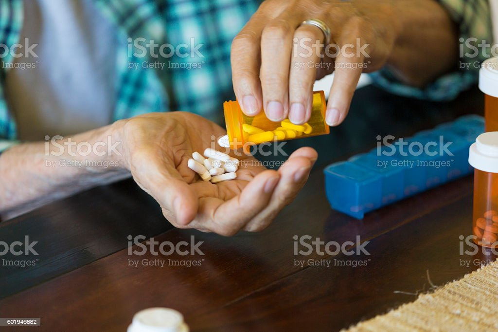 Senior man pours medication into his hand stock photo