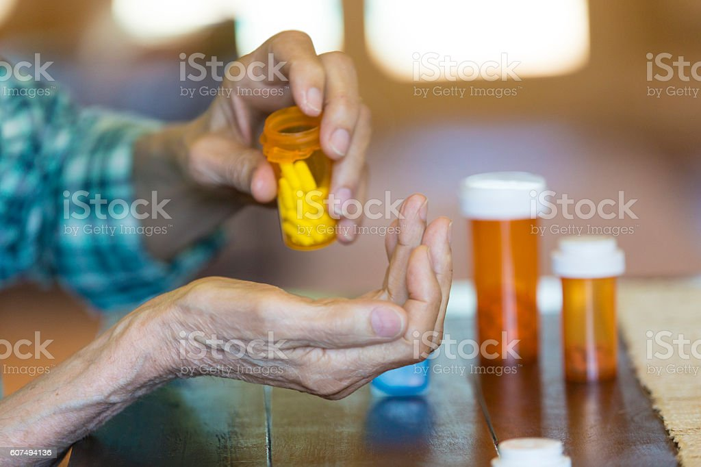 Senior man pours medication into wife's hand stock photo