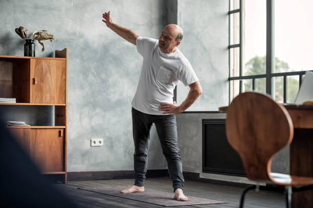Senior man practicing yoga trikonasana pose at the living room stock photo