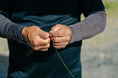 A senior man is preparing fishing rod.