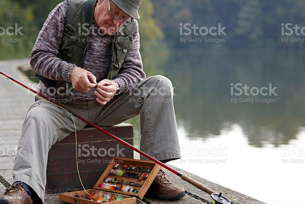 Uomo anziano preparare l'esca per la pesca - foto stock