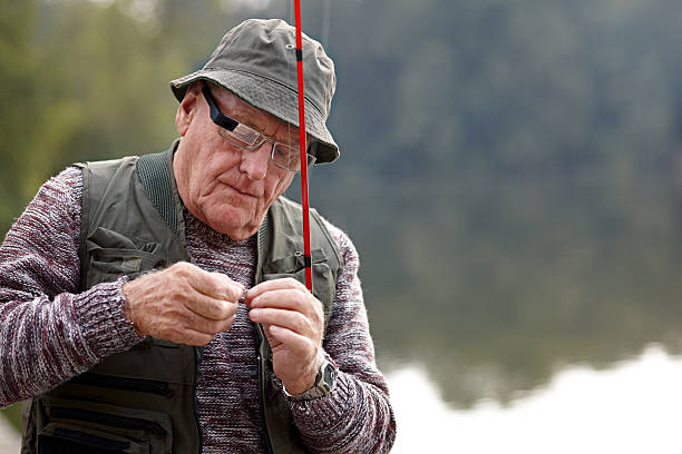 Senior man preparing the bait for fishing Senior man wearing smart glasses putting bait on a hook in preparation for fishing fishing bait stock pictures, royalty-free photos & images