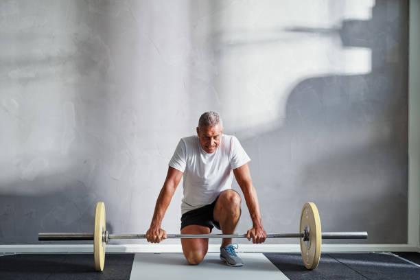 Senior man preparing to lift weights at the gym - foto stock