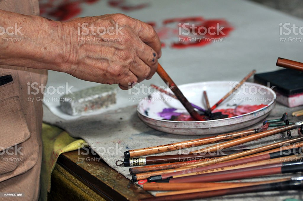Senior man produces traditional Chinese painting stock photo