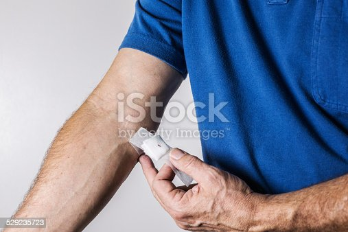 A senior man health labratory patient in a blue polo shirt has just given blood for testing. With the needle wound near the inside of his elbow now just a tiny scab with dried blood, he is pulling off the white bandage tape and sterilized gauze from his arm.