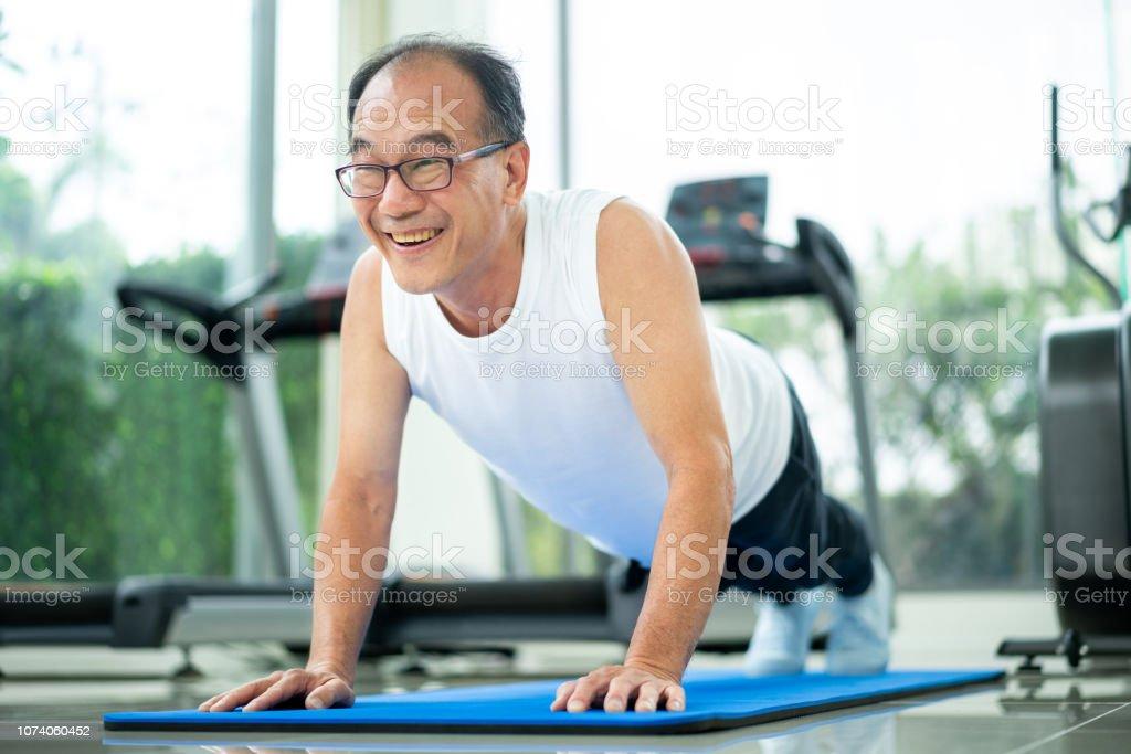 Senior man push up in fitness gym. stock photo