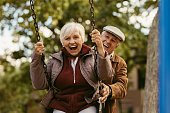 Senior man pushing his female partner on swing in park and having fun together. Playful and happy senior couple enjoying at swing in park .