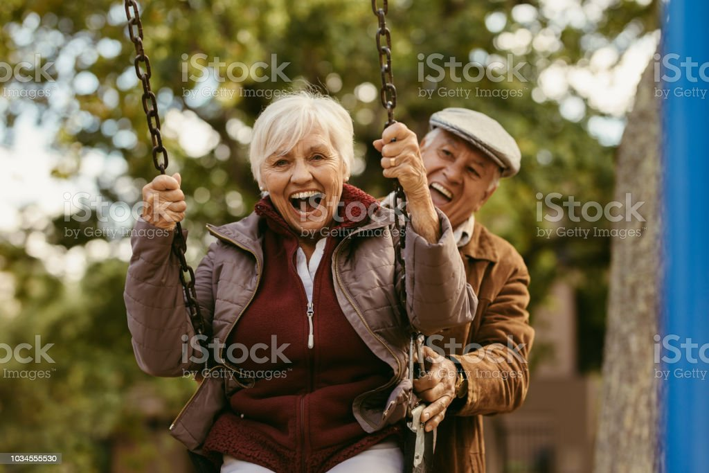 Senior man pushing his partner on swing stock photo