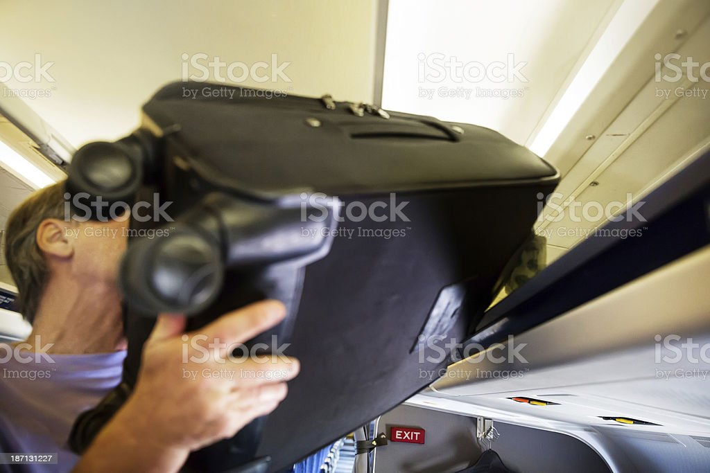 Senior man puts heavy luggage into plane's overhead compartment stock photo