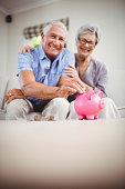 istock Senior man putting coins in piggy bank 675052456