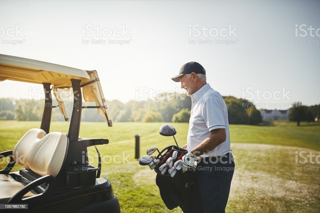 Senior man putting his bag full of clubs on a cart while enjoying a...