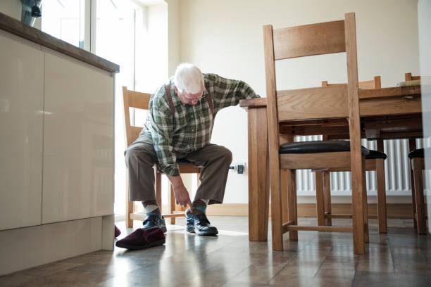 senior man putting on his shoes - old man feet stock photos and pictures