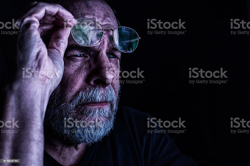 Senior Man Raising Glasses To Better Focus Vision stock photo