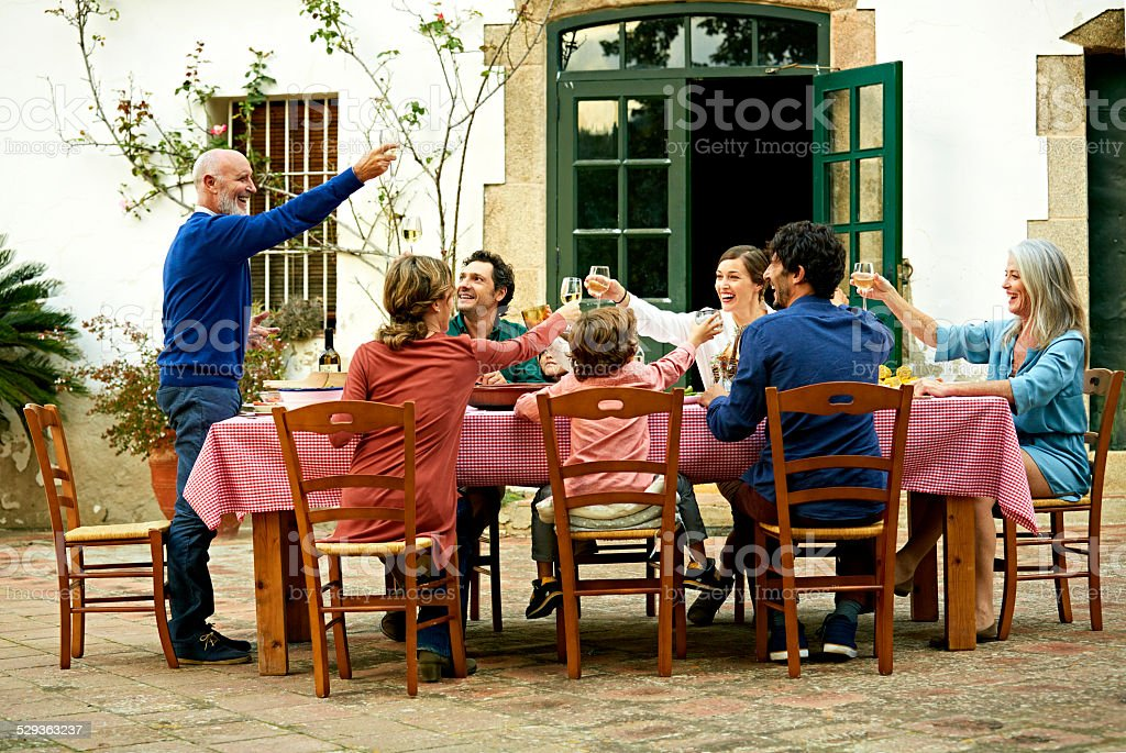 Senior man raising toast to family at meal table stock photo