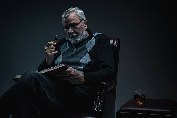 senior man reading a book in dimly lit room - dimly stock pictures, royalty-free photos & images