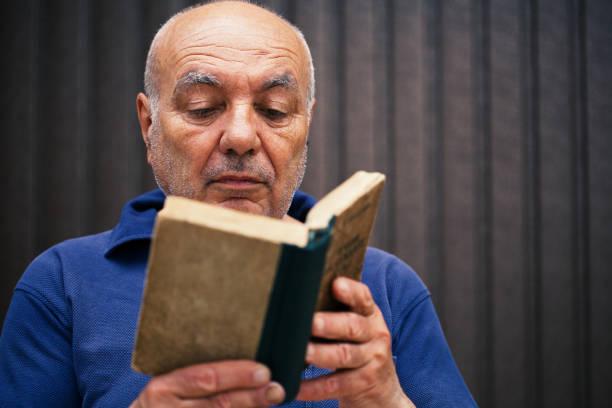 senior man liest ein buch - gedichte zum ruhestand stock-fotos und bilder