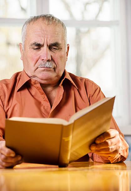 älterer mann liest ein buch - gedichte zum ruhestand stock-fotos und bilder
