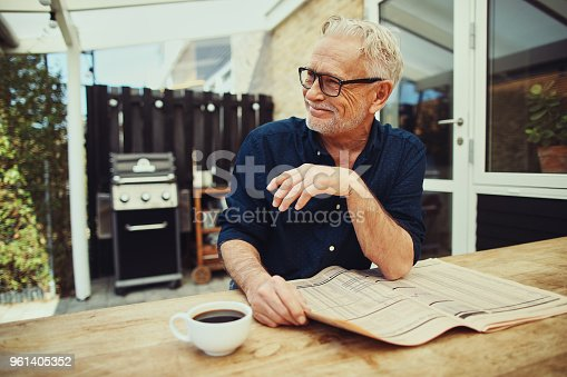 116379055 istock photo Senior man reading a newspaper outside and drinking coffee 961405352