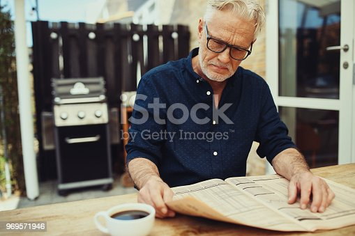 116379055 istock photo Senior man reading a newspaper outside on his patio 969571946