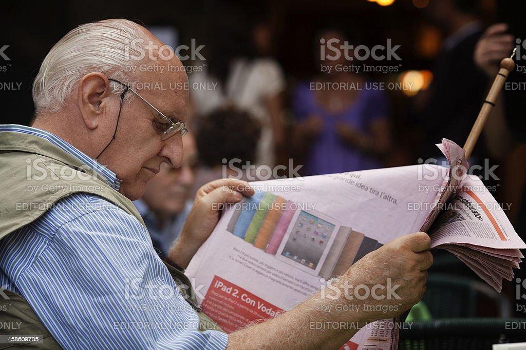 senior man reading an italian newspaper stock photo
