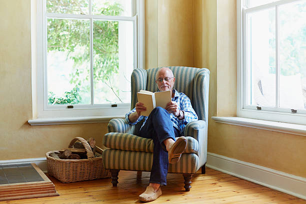 Senior man reading book at home Full length of senior man reading book while relaxing on chair at home armchair stock pictures, royalty-free photos & images