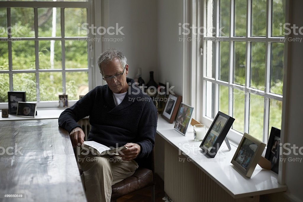 Senior man reading book in cottage stock photo