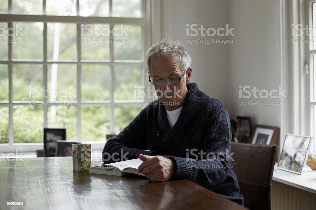 Senior man reading book in cottage stock photo