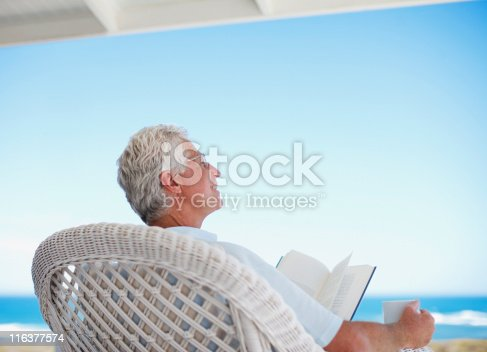 istock Senior man reading book on beach patio 116377574