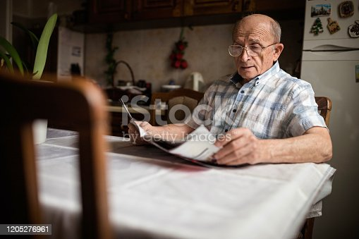 Grandpa in pension relaxing at home while reading a newspaper