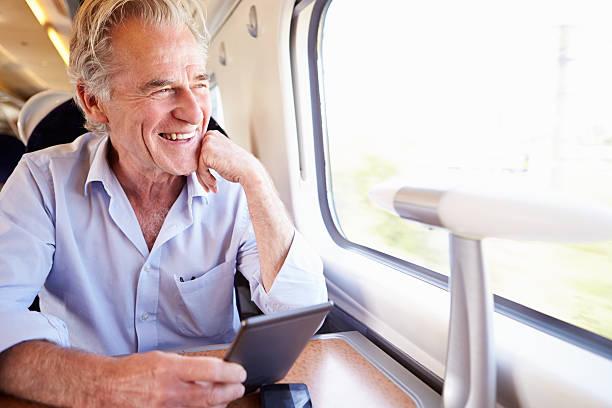 älterer mann liest ein buch auf dem zug e - schnell lesen lernen stock-fotos und bilder