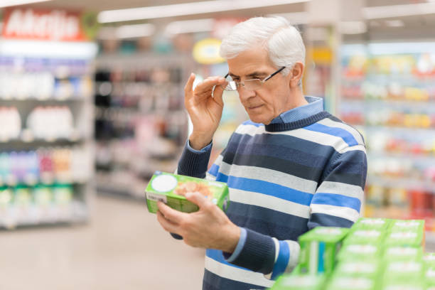 Senior man reading food label at a grocery store Elderly man shopping in local supermarket. He is holding box and reading nutrition label. labeling stock pictures, royalty-free photos & images