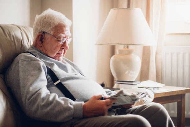senior man reading his newspaper - stomach sitting stock photos and pictures
