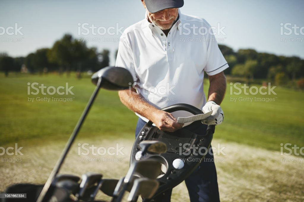 Sporty senior man standing by his clubs and reading his scorecard...