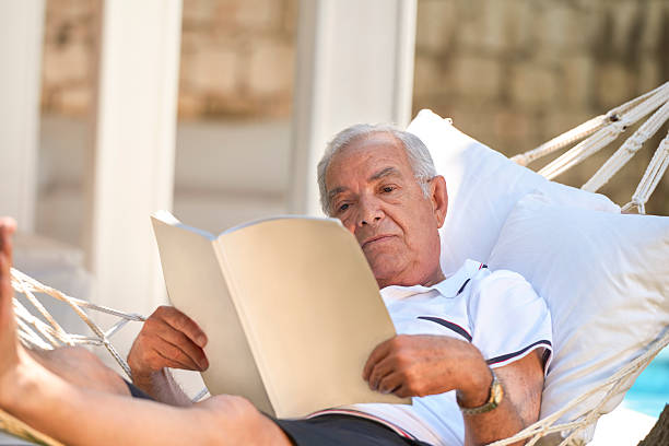 senior man reading magazine in hammock - newspaper beach stockfoto's en -beelden