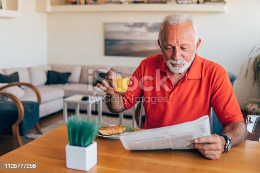 Old man reading newspapers over breakfast