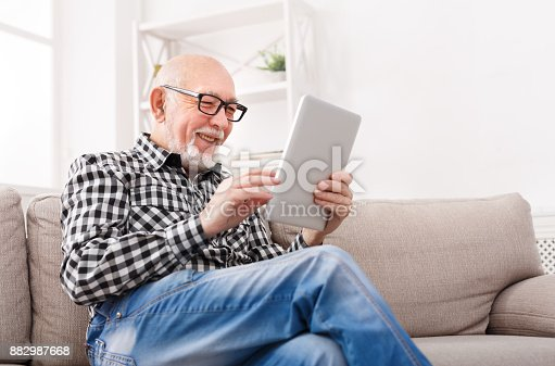 istock Senior man reading news on digital tablet 882987668