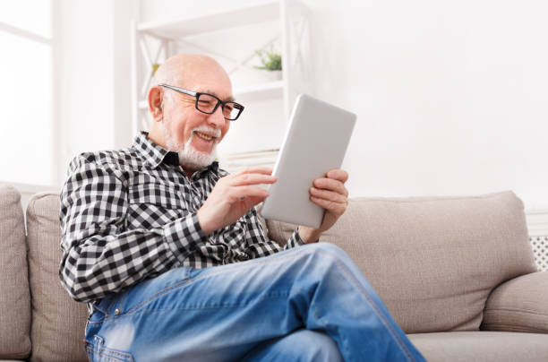 senior man reading news on digital tablet - idosos imagens e fotografias de stock