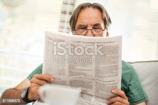 116379055 istock photo Senior man reading newspaper in home 611856372