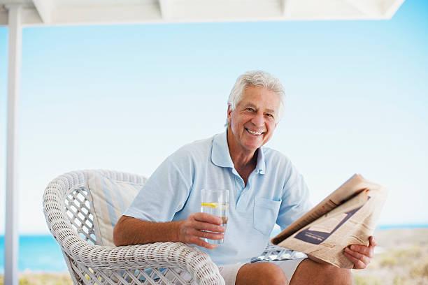 senior man reading newspaper on beach patio - newspaper beach stockfoto's en -beelden